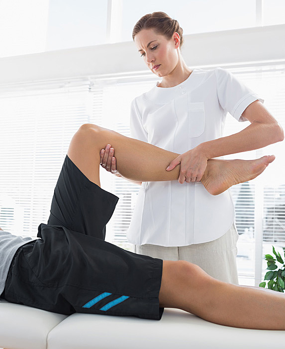Female physiotherapist working on man's leg