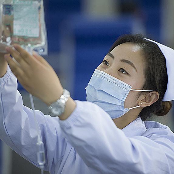 Nurse checking on fluid bag