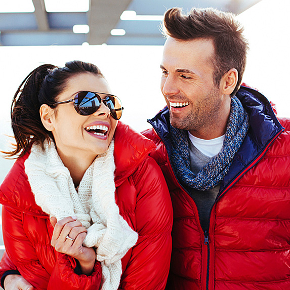 A smiling couple in matching red puffy winter coats sit together outside