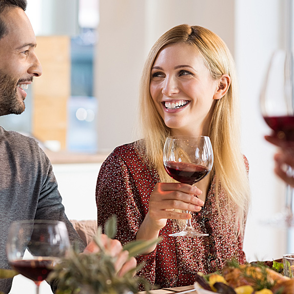 A smiling blonde woman holds a glass of red wine and looks to her partner as they talk over dinner