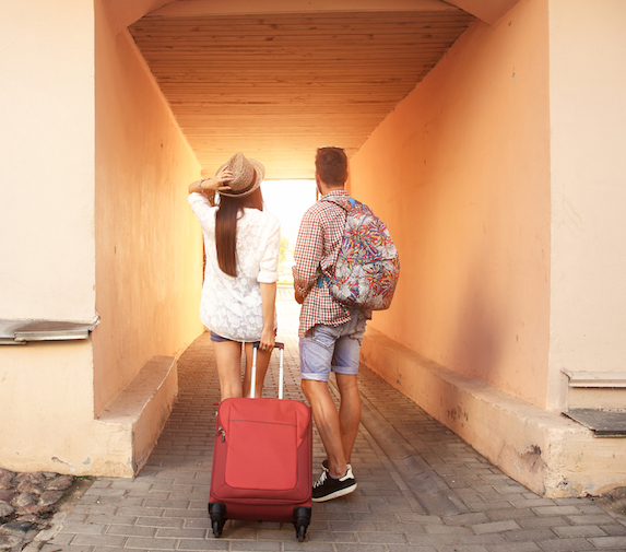 Image of a couple from behind, standing with a red rolling suitcase at the entrance to a tunneled walkway