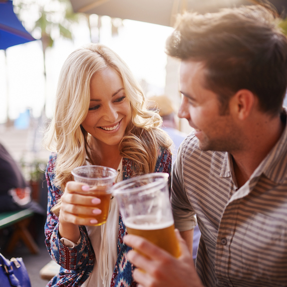 A young couple enjoying drinks on a patio lean in toward one another, smiling