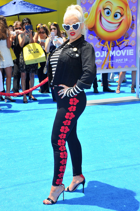 Christina Aguilera poses in black leggings with a red print detail, a striped t-shirt, black jacket and white heart-shaped sunglasses