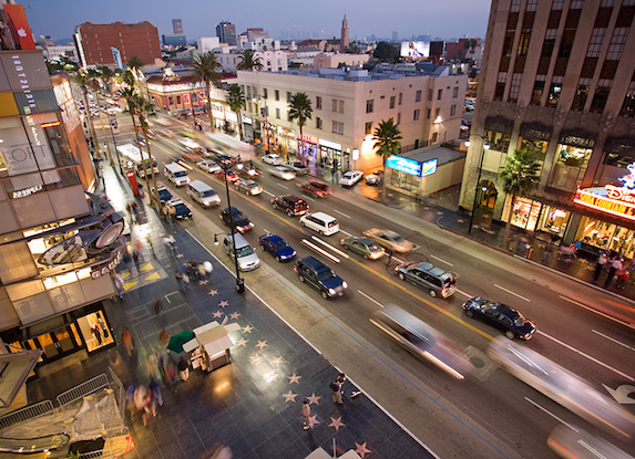 A nighttime view of the busy streets and bright lights of Hollywood Boulevard