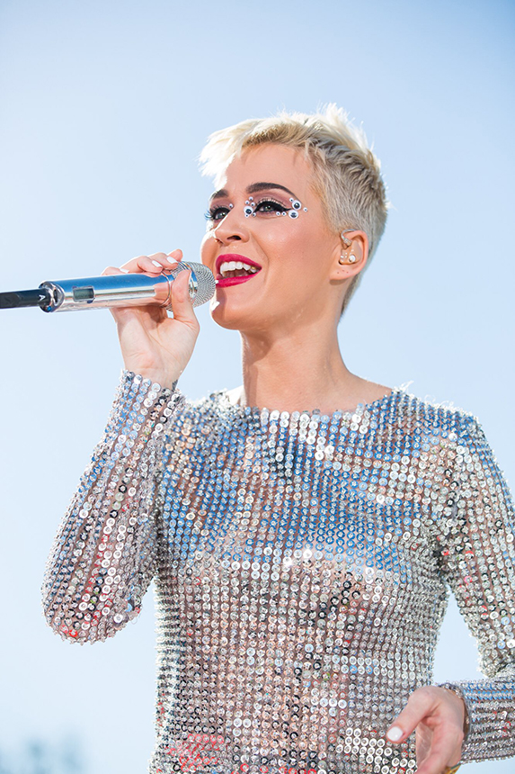 Katy Perry with short blonde pixie hair, singing into a silver microphone while wearing a metallic silver stop and red lipstick.