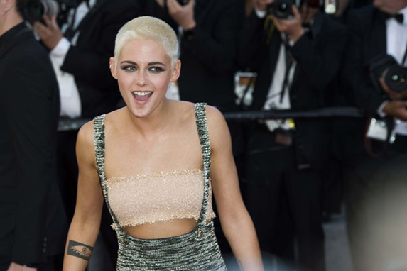 Kristen Stewart laughing with platinum blonde shaved hair on the red carpet