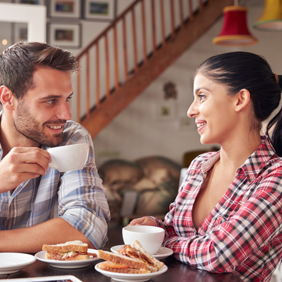 A smiling couple sit chatting over coffee and sandwiches