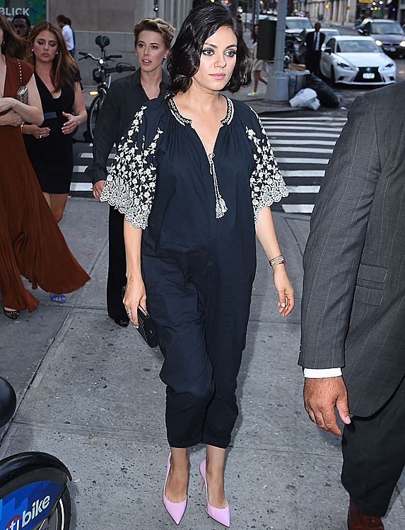Pregnant Mila Kunis wearing a black and white peasant-style jumpsuit and with her hair in a bob.