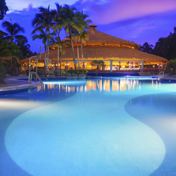 From the hotel pool at night, a large and luxurious tiki hut-style building is lit up and surrounded by palms