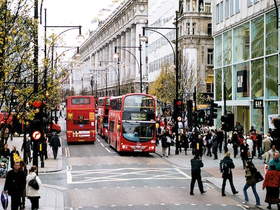 People fill the sidewalks and intersections of busy London, England shopping destination, Oxford Street