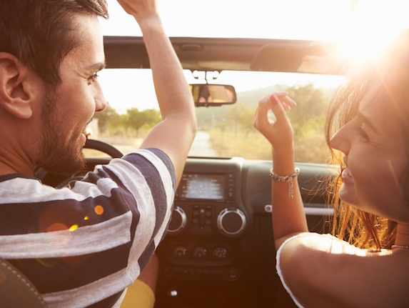 A smiling couple raise their hands up as they look toward each other while driving along a road on a sunny day