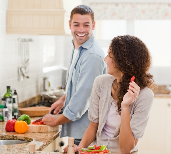 A couple stand together in the kitchen preparing a meal, smiling and looking toward one another