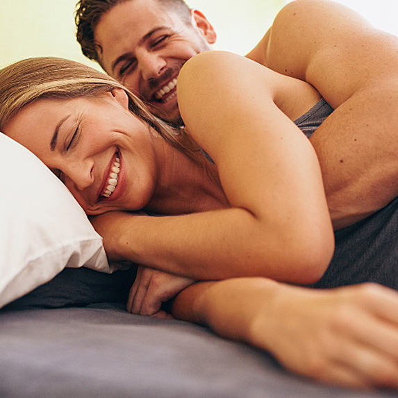 A couple smile and cuddle in bed together in the morning