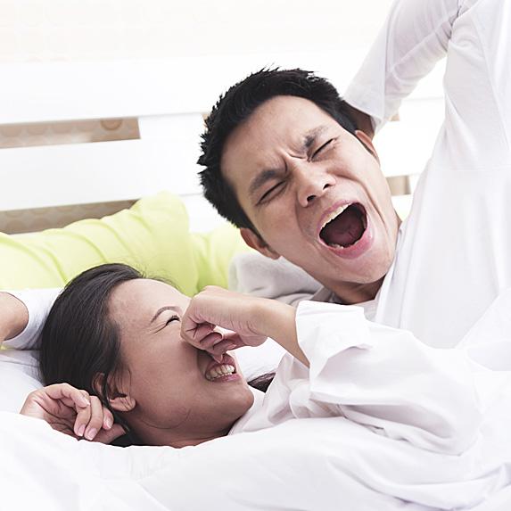 Woman plugging nose as man yawns
