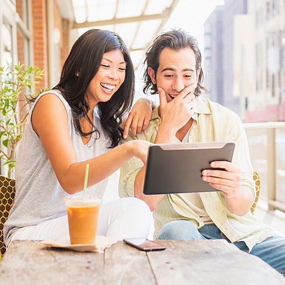 Woman and man looking at tablet over drinks