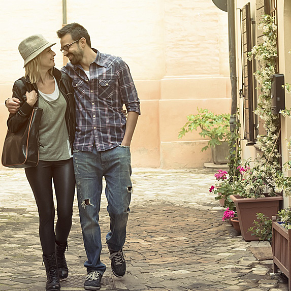 Woman and man walking down street with arms around each other