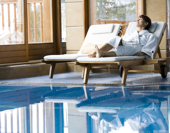 A woman in a robe relaxes while laid out on a lounger by an indoor pool