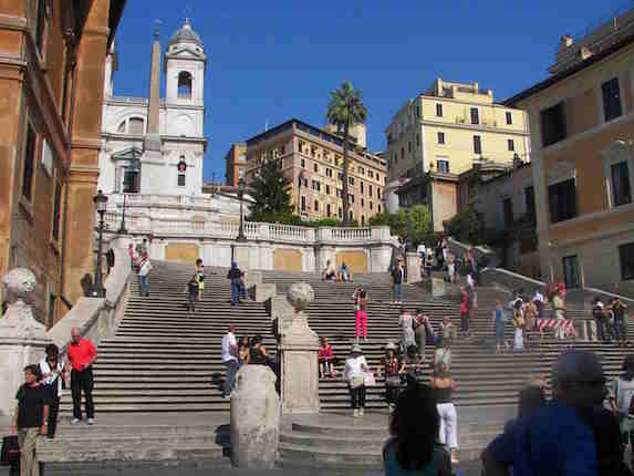 Locals and tourists walk around the Spanish Steps of Rome in Italy