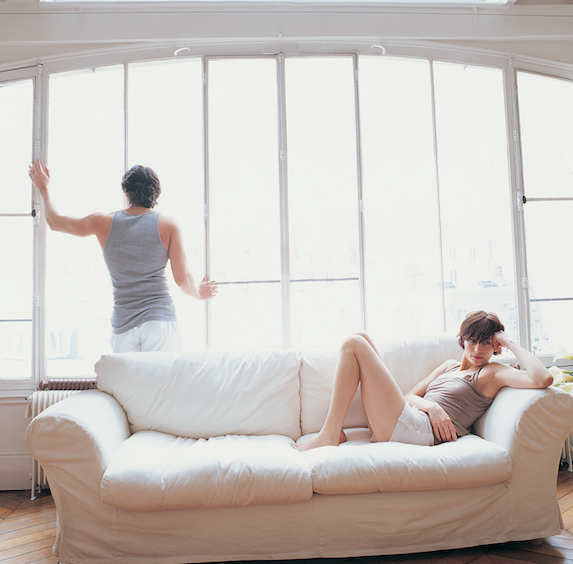 A man stands looking out a window, holding onto the frame with one hand, while a woman sits on a couch looking frustrated with her head in her hands
