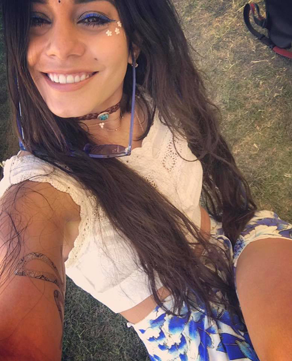 Vanessa Hudgens with waist-long hair, sitting on the grass wearing a white top and blue and white shorts.