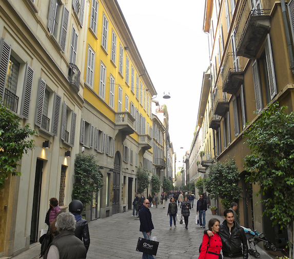 Happy shoppers and tourists stroll the beautiful street of Via Della Spiga, lined with tall colourful buildings