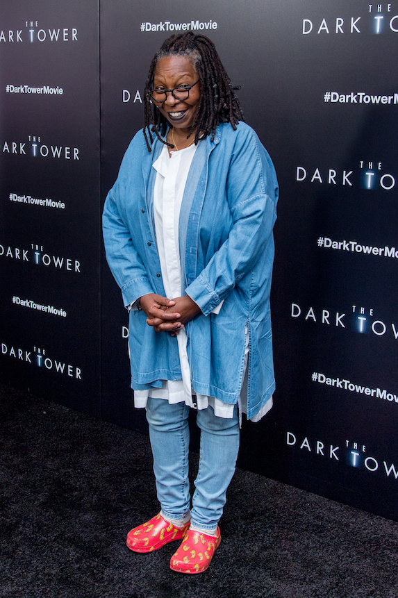Whoopi Goldberg wears a denim top and pants with red Croc-brand shoes on the red carpet