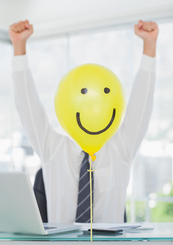 Happy face balloon in front of man
