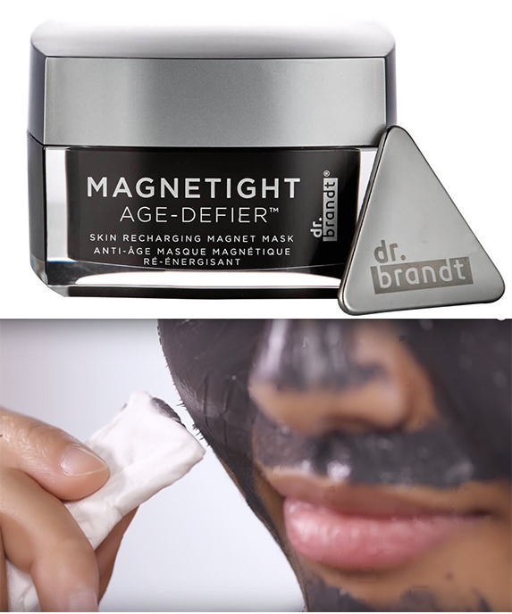 A black and silver tub of skincare and a woman with black face mask on using a small white tool to remove it.