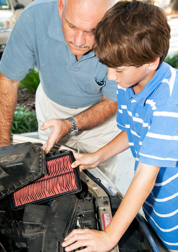Father and son cleaning air filter