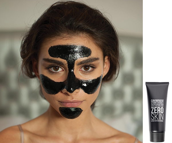 Attractive young brunette woman with shiny black skincare product on her face.