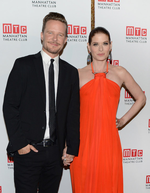 Dressed in their red carpet best, husband Will Chase stands alongside his wife, actress Debra Messing