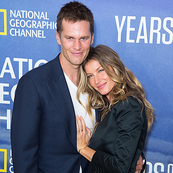 Snuggled in toward one another, lovebirds Tom Brady and Gisele Bundchen are photographed at an event