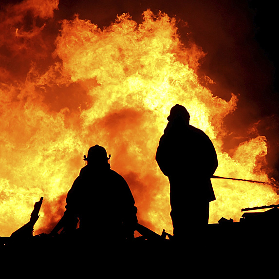 Silhouette of two firefighters in front of huge flames