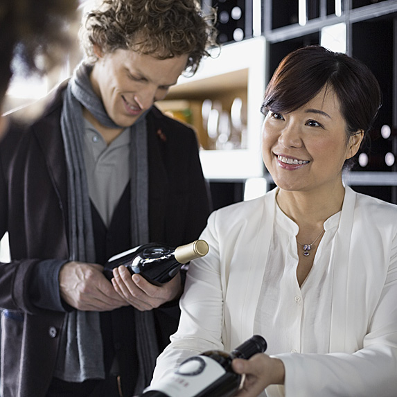 Woman helping couple pick out wine