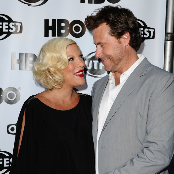 Husband and wife Dean McDermott and Tori Spelling look at each other lovingly while being photographed at an event