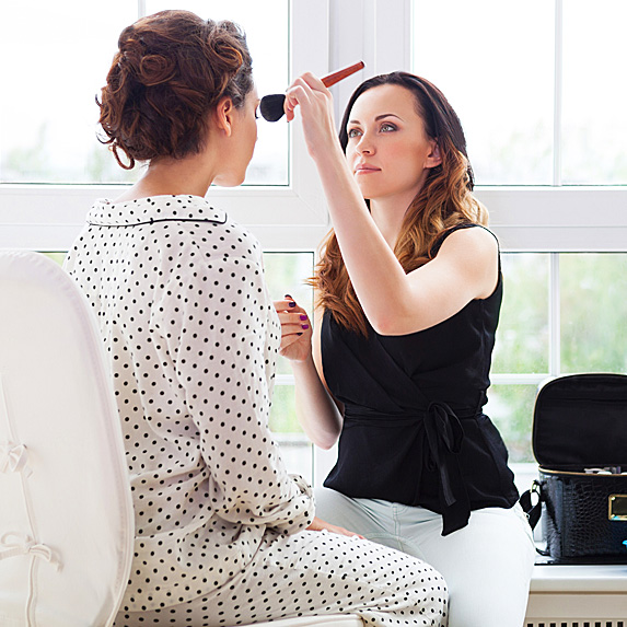 Woman doing another woman's makeup