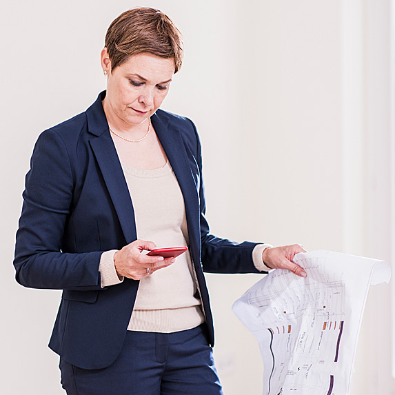 Woman looking at phone, holding house plans