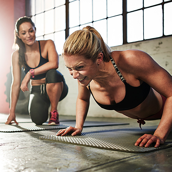 Woman watching another woman doing pushups