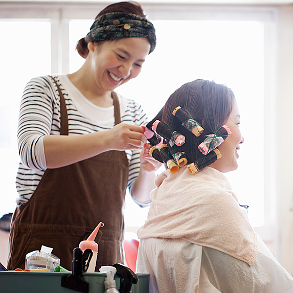 Woman working on another woman's hair
