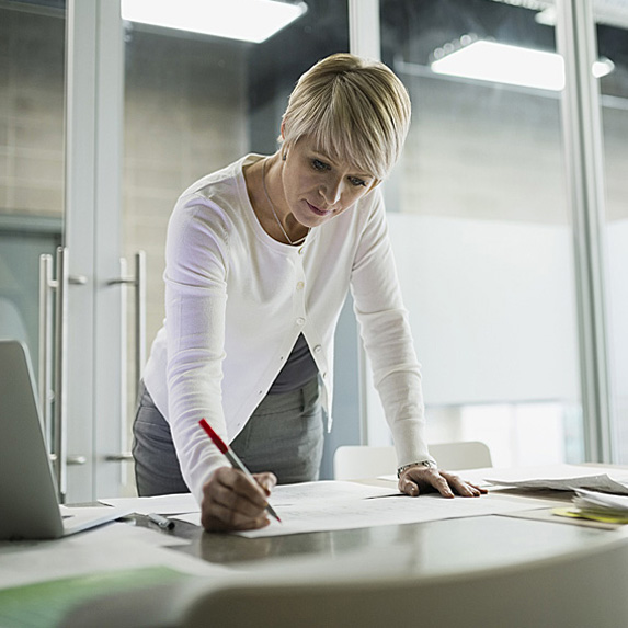 Woman standing at desk, writing