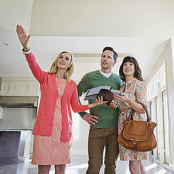 Realtor showing man and woman a house