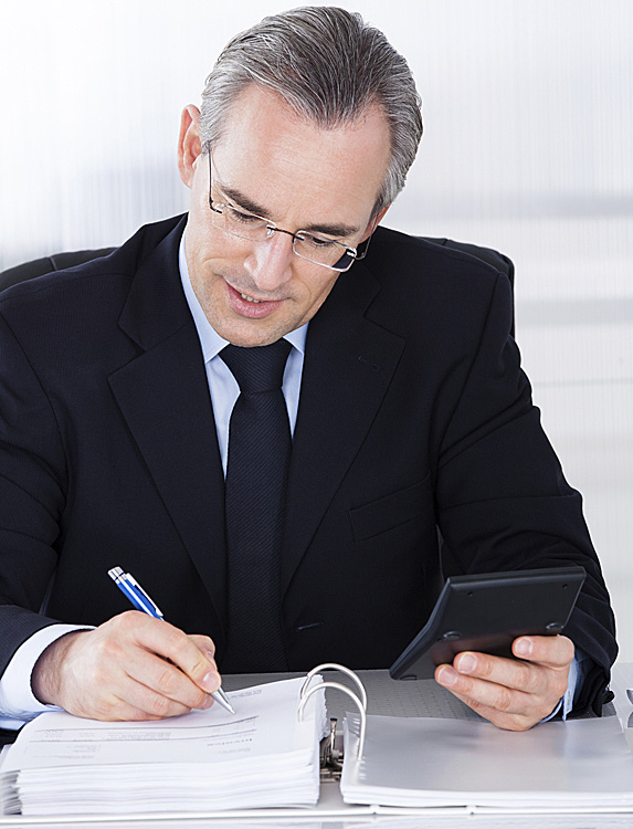 Man writing notes while using a calculator