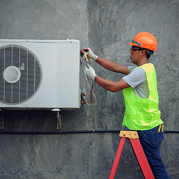 Man working on outdoor air conditioning unit