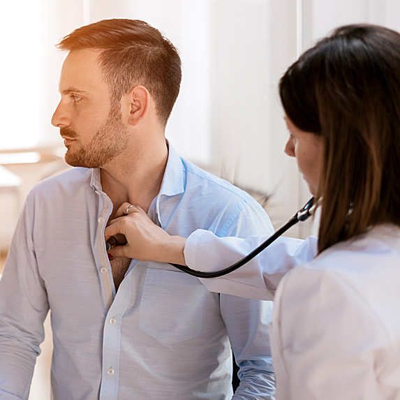 Woman putting stethoscope on man's chest