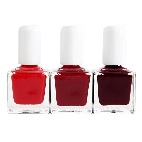 Three bottles of different shades of red nail polish on a white background.