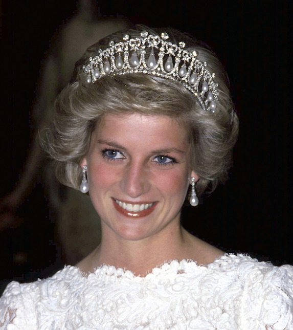 Princess Diana smiles, dressed in white and wearing the Cambridge Knot Tiara, given to her by the Queen