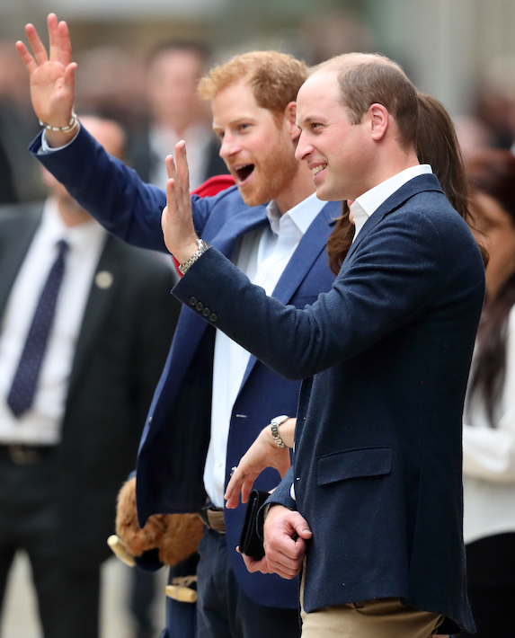 Prince William and Prince Harry wave to the crowds while attending an event