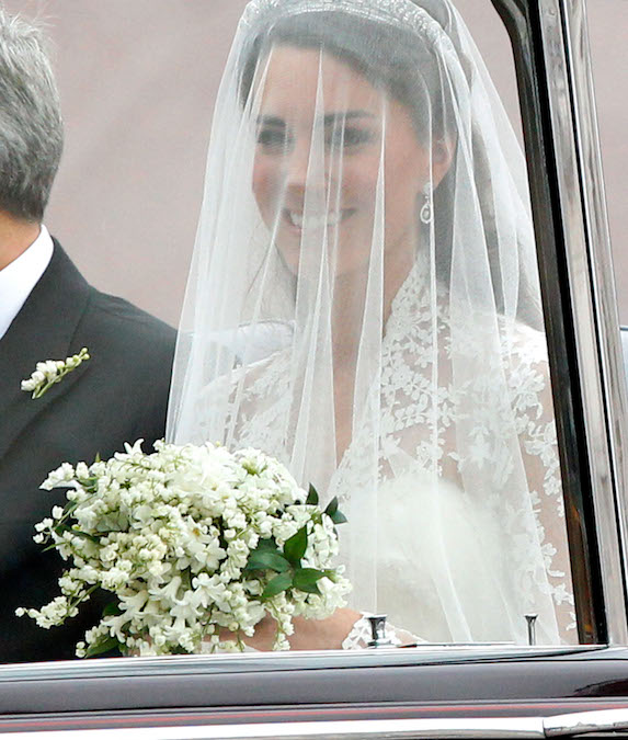 Kate Middleton holds her bouquet as she sits in the passenger sit of a car on her wedding day in 2011