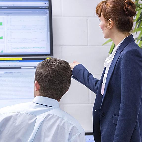 Woman and man looking at monitors