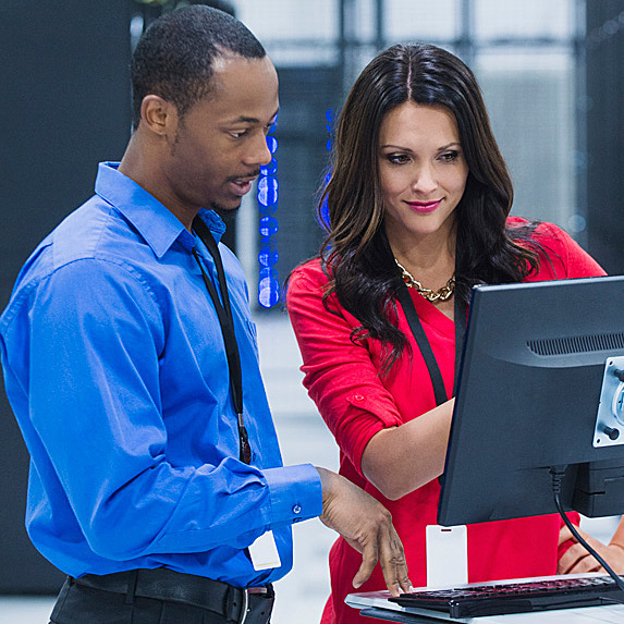 Man and woman standing, looking at monitor